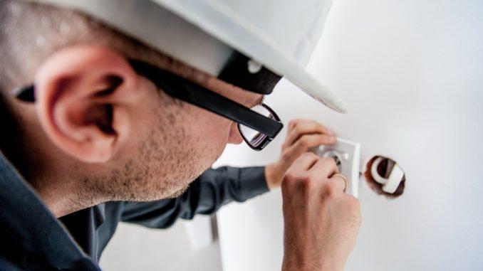 אדם בוחן תשתית חשמל, מהדק חשמל
