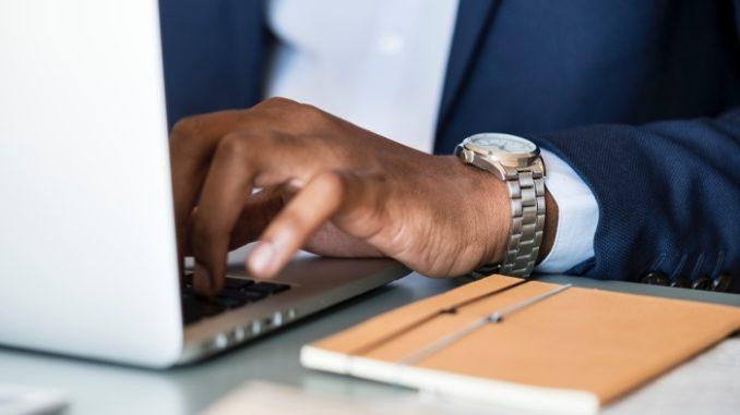 גבר יושב מול ממחשב נייד ומקליד