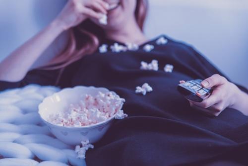 אישה נהנית מקערת פופקורן מול הטלויזיה. הצטרפות ליס